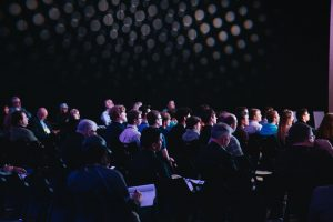 People attending a conference in a darkened auditorium